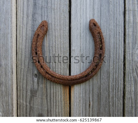 Rusty Horse Shoe Attached to a Rustic Wooden Door in Rural Devon, England, UK #625139867