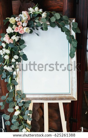 White picture in a frame covered with rose garland