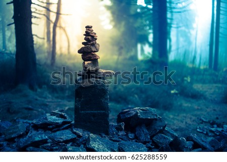 Piled good luck stones showing the way for lost ones in enchanted forest. Beautiful mysterious woods landscape background in Czech Orlicke Hory mountains - Magical fog light Happy Halloween card #625288559