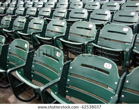 Rows of empty wet green stadium seats, seats number 13, 12, 11. AT&T Park San Francisco #62538037