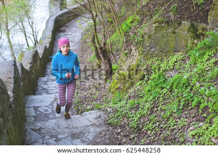 The woman running the stairs in the Park. The girl goes in for sports in the nature. Jogging in the spring woods. #625448258