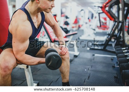 Persistent young man training in a gym #625708148