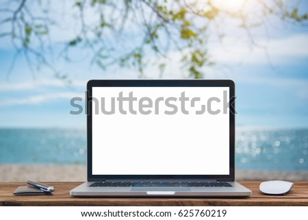 Computer notebook and mouse with a picture Sea view scenery Blur sea background,Blur summer white sand beach with sparkling sea water
