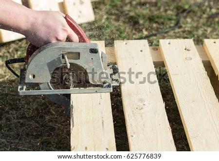 Man crosses wooden boards with an electric saw. sunny day. copy space. #625776839