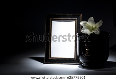 Black evangelical urn with blank mourning frame, and flower on dark background