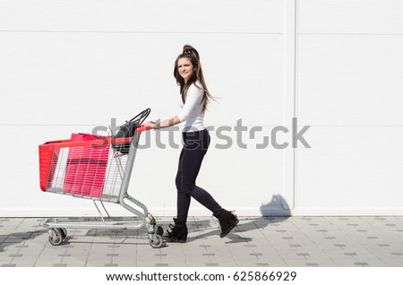 beautiful long-haired girl or young woman pushing a shopping trolley in front of a blank white wall #625866929