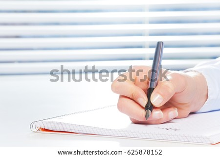 Hand writing with fountain pen at the table #625878152