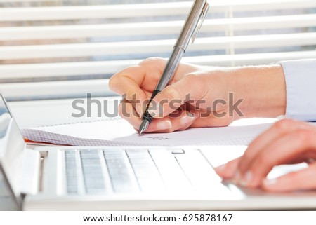 Hand writing with a pen while working on computer #625878167