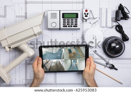 Close-up Of A Person Watching Footage On Digital Tablet With Security Equipments On Blueprint Royalty-Free Stock Photo #625953083