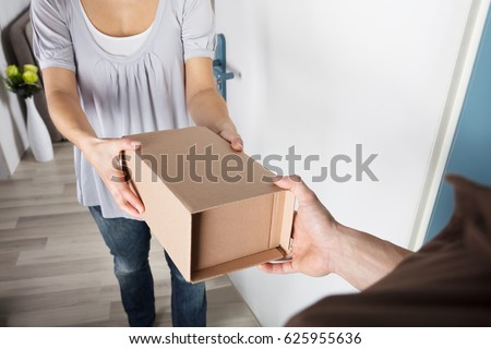 Close-up Of Woman Taking Cardboard Box From Delivery Man #625955636