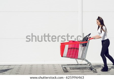 pushing shopping carts in front of a white wall in a shopping center outdoors #625996463
