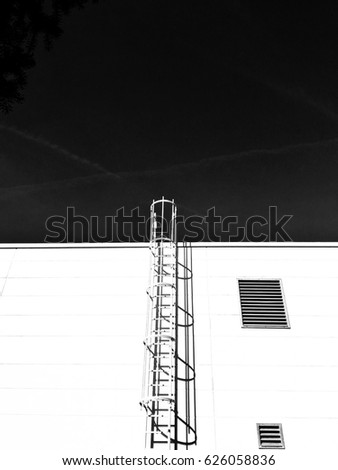 black and white photography industrial wall with steel roof ladder