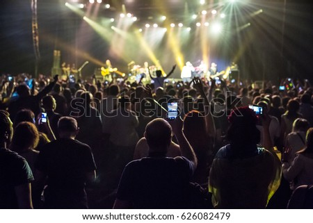 Crowd at concert and blurred stage lights . Close up of photographing with smartphone during a concert . #626082479