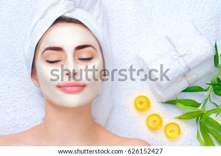 Spa Woman applying Facial clay Mask. Beauty Treatments. Close-up portrait of beautiful girl with a towel on her head applying facial mask. Royalty-Free Stock Photo #626152427