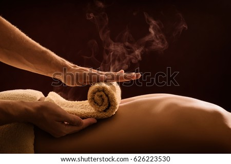 A professional therapist applies a hot towel on the back of a man. Hot towel compress. SPA treatment Royalty-Free Stock Photo #626223530