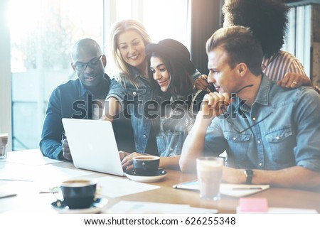 Woman showing coworkers something on laptop computer as they gather around a conference table #626255348