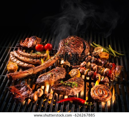 Assorted delicious grilled meat with vegetables over the coals on a barbecue Royalty-Free Stock Photo #626267885