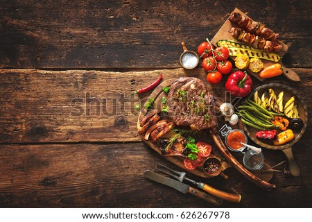 Grilled meat and vegetables on rustic wooden table #626267978