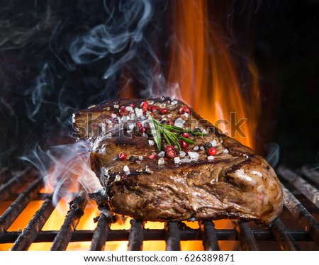 Tasty Beef steaks on the grill with fire flames #626389871