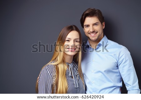 Happy attractive young couple posing arm in arm against a dark grey background with copy space looking at the camera with friendly pleased smiles