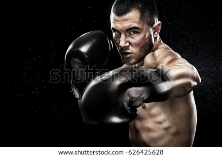 Sportsman muay thai boxer fighting in boxing cage. Isolated on black background with copy Space. Royalty-Free Stock Photo #626425628