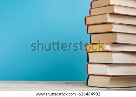 Stack of books on wooden table on blue wall background. Copy space for text.Back to school. Education concept. #626484902