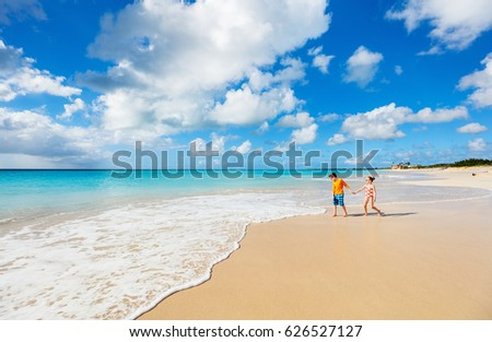 Kids having fun at tropical beach during Caribbean summer vacation playing together at shallow water #626527127