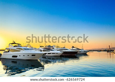 Luxury yachts docked in sea port at sunset. Marine parking of modern motor boats and blue water. Tranquility, relaxation and fashionable vacation. Royalty-Free Stock Photo #626569724