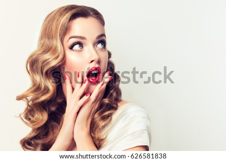 Shocked and surprised girl screaming and  looking to the side presenting  your product . Curly hair woman amazed .Beautiful girl  with curly hair and red nails manicure. Expressive facial expressions Royalty-Free Stock Photo #626581838