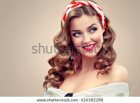 Beautiful retro vintage pin-up girl . Beautiful girl  with curly hair  pointing to the side . Presenting your product. Expressive facial expressions #626582288