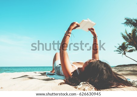 Leisure in summer - Young women lying on a tropical beach, relax with book. Blue sea in the background. Summer vacation concept. vintage color tone. #626630945