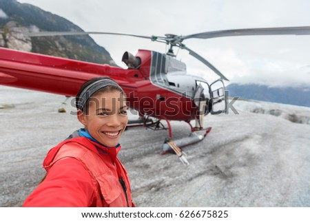 Happy tourist taking selfie picture on helicopter tour excursion. Asian woman cruise passenger on shore activity glacier walk hike in Alaska, USA.