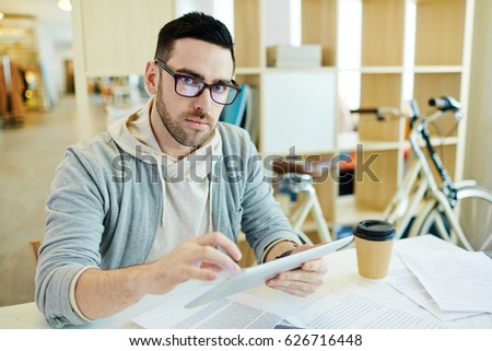 Portrait of confident handsome business man dressed in casual clothes working with tablet in creative office space and looking at camera #626716448