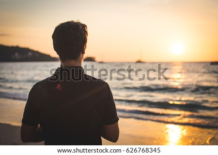 Rear view of a young man admiring the sunset on the beach #626768345
