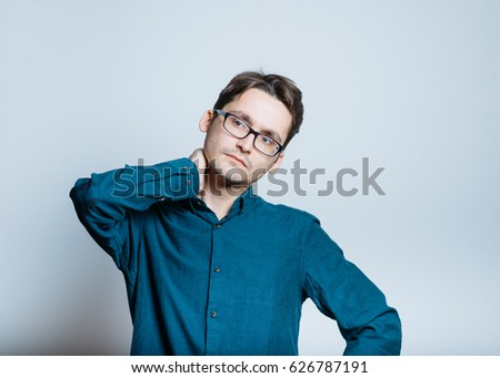 handsome man has a sore neck, isolated on a gray background