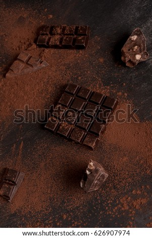Top view of a dark chocolate bar pieces covered in milk chocolate powder over wooden surface #626907974