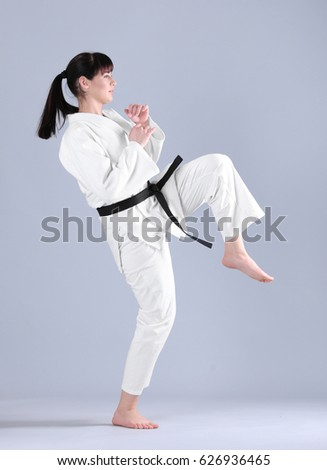 Young sporty woman practicing martial arts on light background #626936465