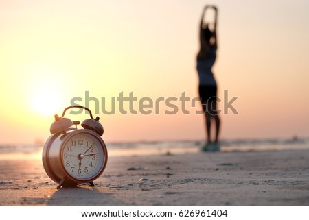 Morning of a new day, alarm clock woman playing yoga and stretching muscles on the beach sunlight in morning. #626961404