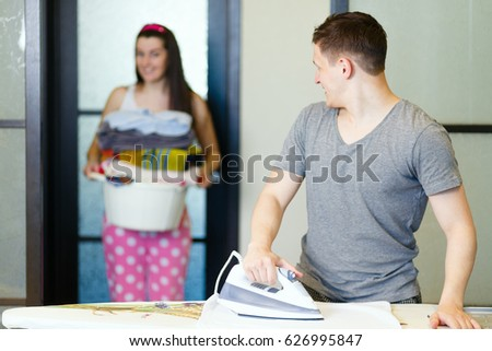 A young man irons clothes.The young man doing house chores.The guy in home clothes irons.A girl carries the Laundry for Ironing