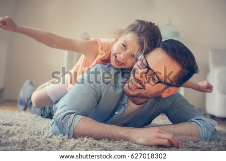 Father and daughter spending time at home. Little girl lying on fathers back with open arms. Looking at camera. #627018302