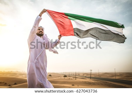 Arabian man walking  in the desert at sunrise #627043736