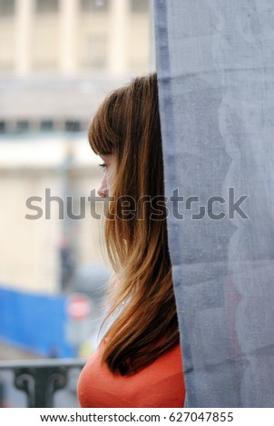 The girl behind the curtain looks out the window #627047855