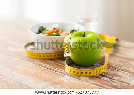 diet, healthy eating, food and weigh loss concept - close up of green apple and measuring tape with salad on wooden table #627075779
