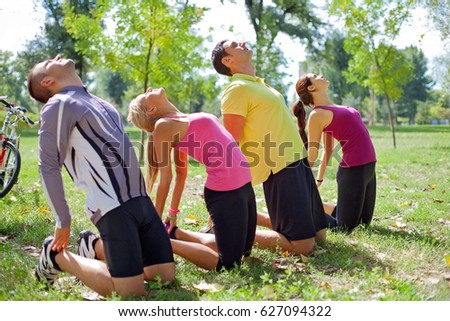 Group of people stretching out in the park on a morning sunshine #627094322