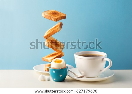 Fresh delicious breakfast with soft boiled egg, crispy toasts and cup coffee or tea on blue background. Levitation food concept. Vintage retro style #627179690