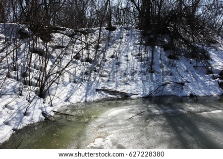 Melting ice on a small forest lake in the sunny April day #627228380