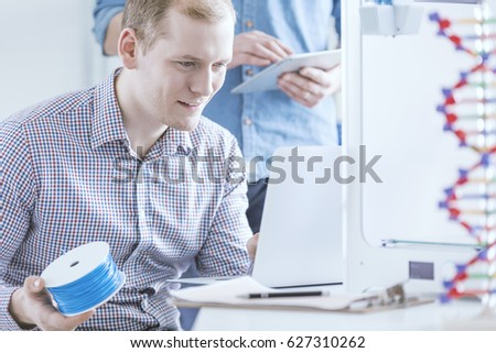 Man holding filament roll preoccupied with 3D printing #627310262