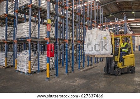 TENERIFE, CANARY ISLANDS - FEBRUARY 24, 2016: Operator with forklift, moving merchandise, in a warehouse of the industrial zone #627337466