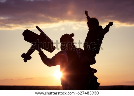 Father and son playing with cardboard toy airplane in the park at the sunset time. Concept of friendly family. People having fun outdoors. Picture made on the background of dark blue sky.
