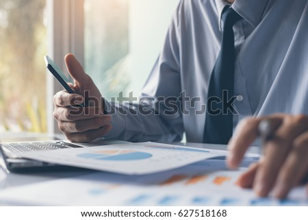 Business man using smartphone and working on laptop computer analysis business data, information review, business strategy analysis concept, technology in smart business #627518168